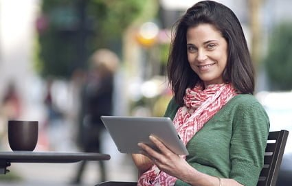 A smiling woman working on her tablet computer at an outdoor cafe